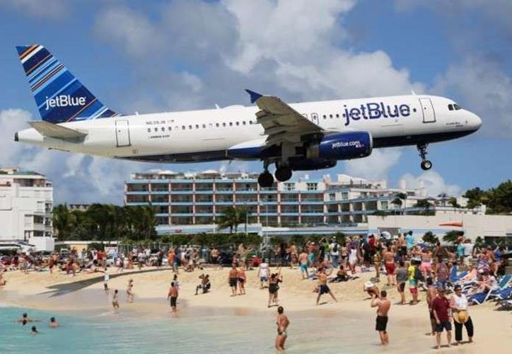 La imagen de bañistas en la playa de Maho, en la isla caribeña de Sint Maarten, contemplando el paso de los aviones a escasos metros de sus cabezas se ha popularizado en todo el mundo. (Contexto/Internet)