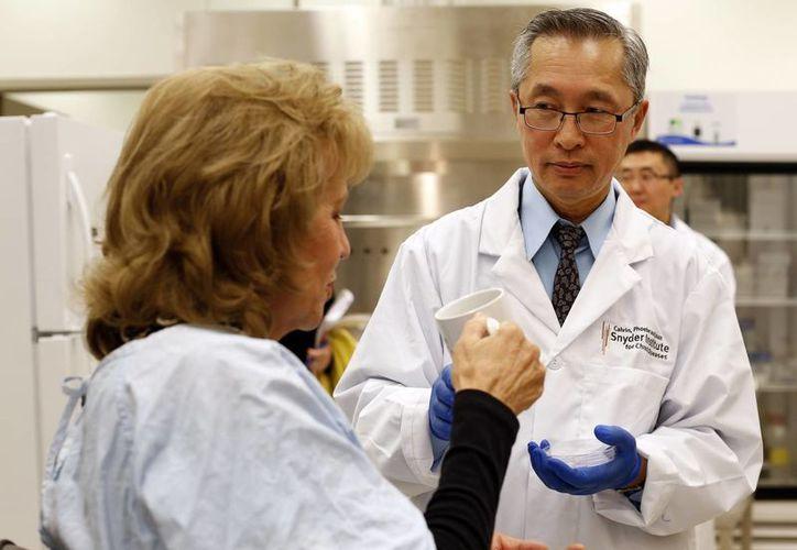 El Dr. Thomas Louie entrega las cápsulas fecales a una paciente en su laboratorio en Calgary, Alberta, Canadá. (Agencias)