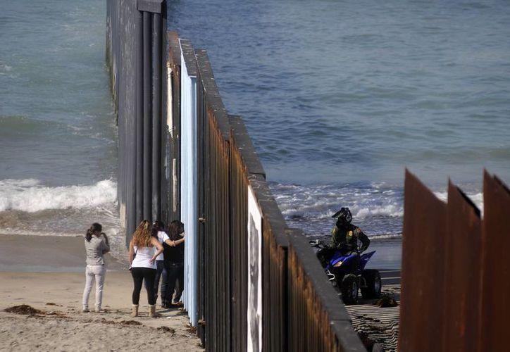 Visitantes de las Playas de Tijuana platican con agentes de la patrulla fronteriza, a través del muro que divide a México y EU. (Archivo/Notimex)