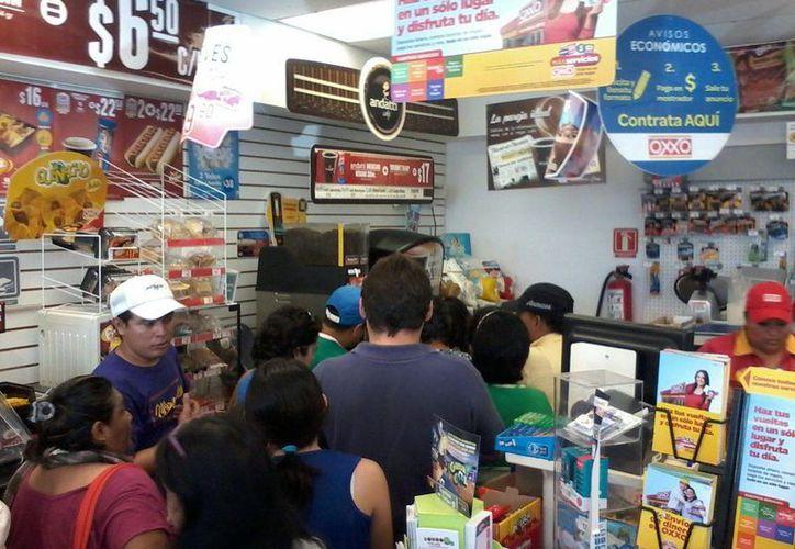 Imagen de la fila que hicieron los ciudadanos en la tienda Oxxo para pedir su café gratis tras emitir su voto. (Coral Díaz/SIPSE)
