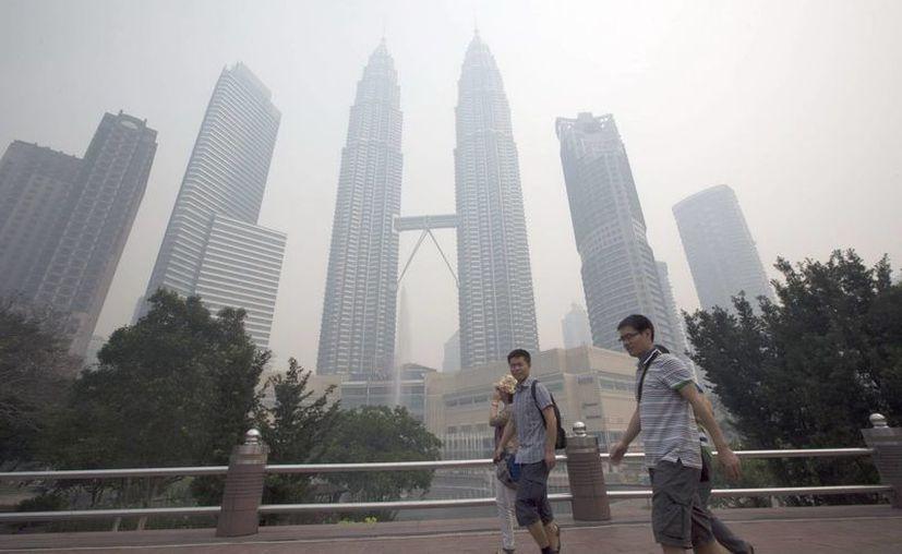Varias personas caminan por un parque cercano a las Torres Petronas, apenas visibles por la contaminación que afecta a Kuala Lumpur. (EFE)