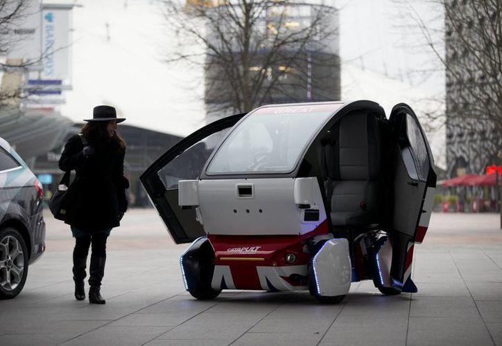 Una mujer posa para la cámara junto a un prototipo de automóvil sin chofer llamado LUTZ Pathfinder Pod durante el lanzamiento cerca de la arena O2 en Londres. (Agencias)