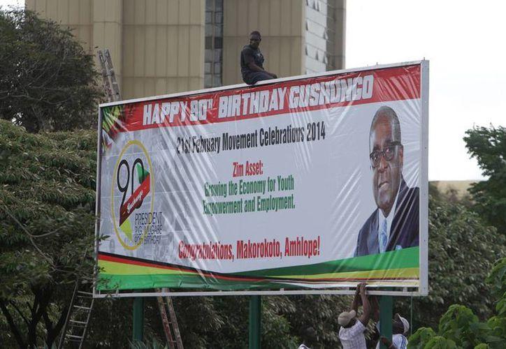 Trabajadores colocan un anuncio espectacular que contiene una felicitación para el 'eterno' presidente de Zimbabue, Robert Mugabe. (Agencias)