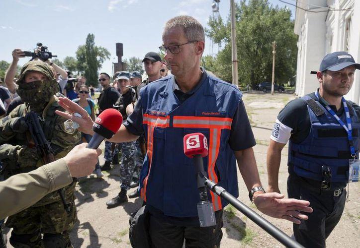 Peter Van Vilet, al centro, líder del equipo de expertos forenses holandeses en Ucrania, sale de un encuentro con reporteros tras inpeccionar un tren refrigerado cargado con los restos de las víctimas del Vuelo 17 de Malausia Airlines. (Agencias)