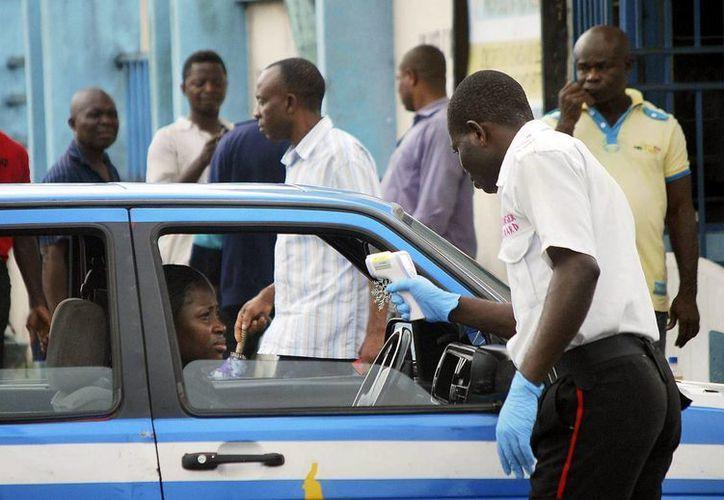 Personal sanitario usa un termómetro por control remoto para examinar a la conductora de un vehículo por si presentara los síntomas del ébola, en la ciudad de Port Harcourt, Nigeria. (EFE))