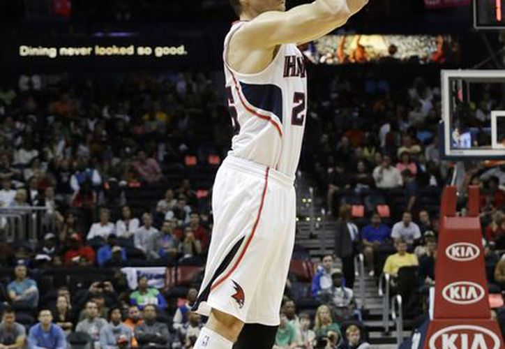Kyle Korver, de los Hawks, se eleva para encestar el triple con el que impuso nueva marca de triples consecutivos en la NBA. (Agencias)