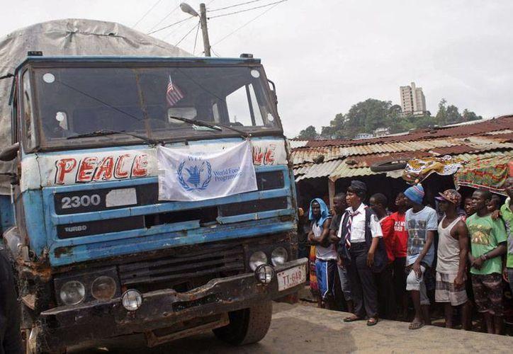 Pobladores de Liberia esperan la descarga de un camión cargado de alimentos provenientes de ayuda humanitaria. Liberia es uno de los países más afectados por el ébola. (AP)