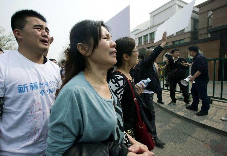 Familiares chinos de pasajeros del avión de la compañía Malaysia Airlines desaparecido el 8 de marzo se manifiestan afuera de la embajada de Malasia en Beijing. (Agencias)
