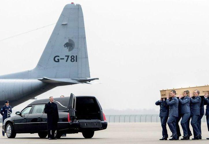 A un lado de un avión militar se aprecia el traslado de víctimas del avionazo en Ucrania, ocurrido el 17 de julio del año pasado. (EFE)