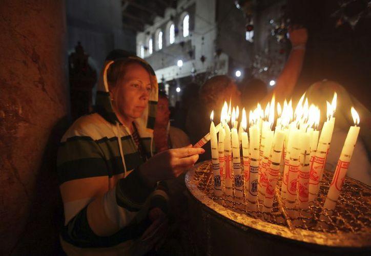 Una mujer enciende velas en la iglesia de la Natividad de Belén, donde la tradición cristiana afirma que nació Jesús de Nazaret. (EFE)