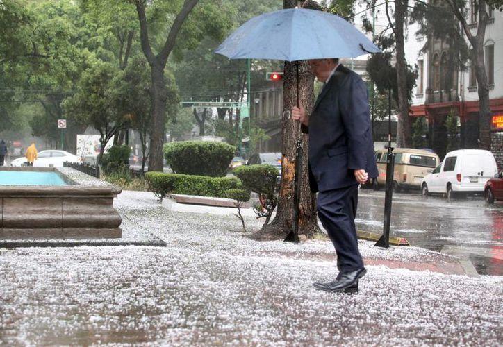 Las autoridades capitalinas recomiendan precaución al transitar en las calles debido a la intensa caída de granizo. (Notimex)