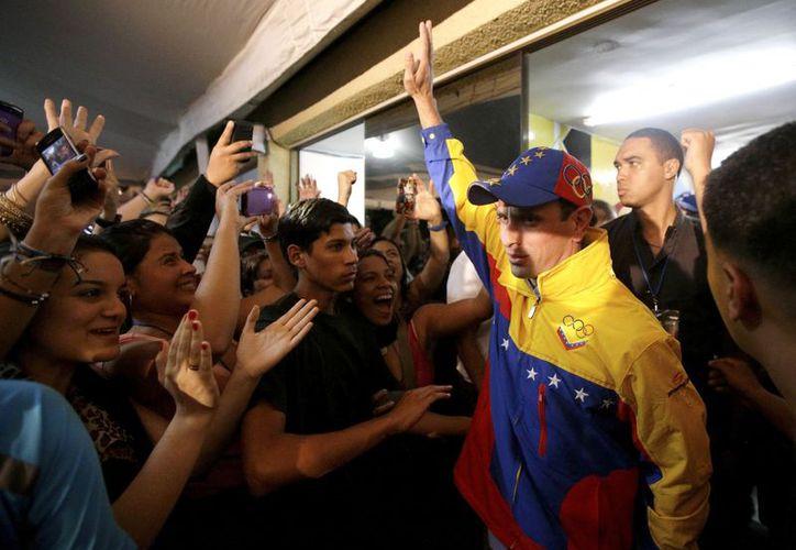 El gobernador de Miranda, Henrique Capriles, saluda a sus seguidores tras ser reelegido. (Agencias)