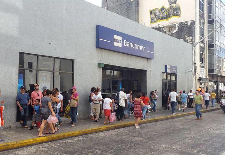 Imagen de un banco en el centro de Mérida, en donde se reporta un lleno total en cajas y atención al cliente, este 22 de diciembre de 2014. (Cristian Cuxim/Milenio Novedades)