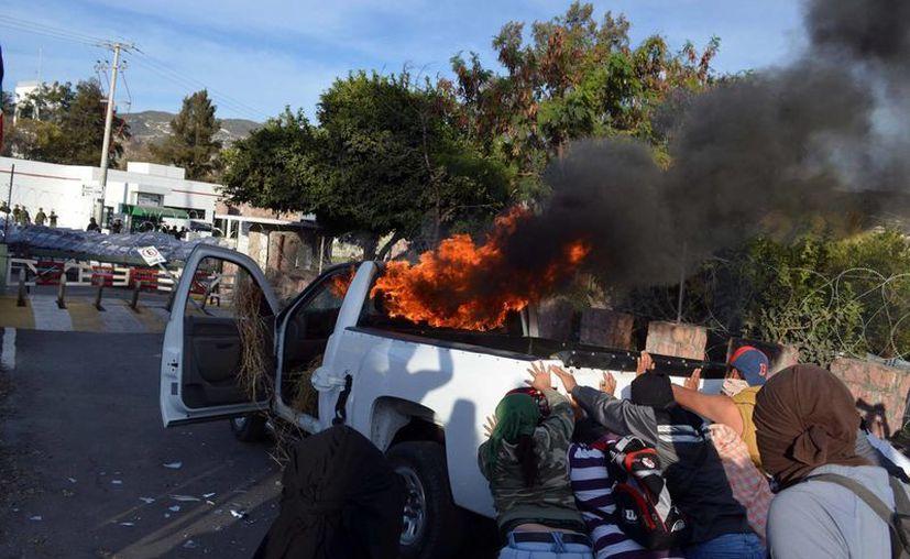 Un grupo de personas intenta empujar una camioneta hacia la entrada del cuartel del Ejército en Chilpancingo, Guerrero, donde ayer se dio el enfrentamiento. (Foto: AP)