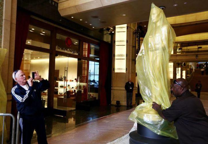 Un trabajador levanta una de las estatuas que serán utilizadas durante la ceremonia en los Oscar. (Agencias)
