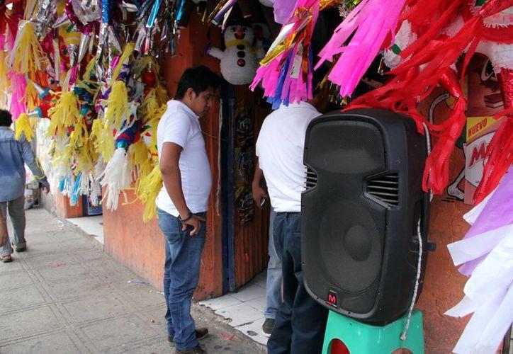 Muchos comercios sacan a las puertas de sus negocios grandes bocinas. (José Acosta/SIPSE)