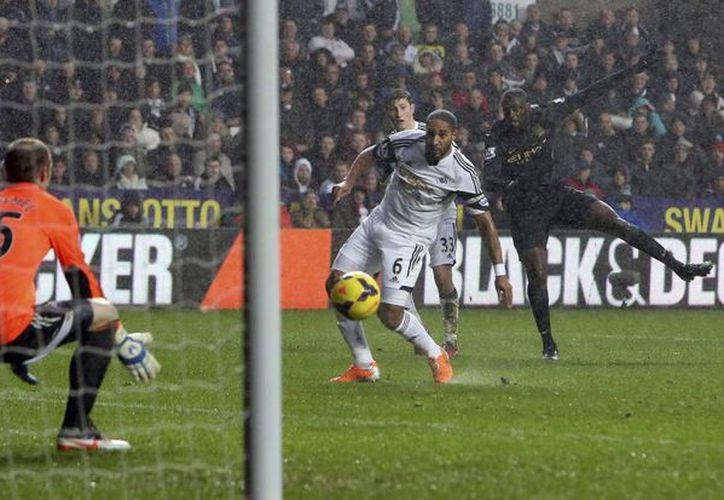 El centrocampista marfileño del Manchester City Yayá Touré (c) marca un gol durante el partido de la Premier League inglesa que enfrentó a su equipo contra el Swansea en el estadio Liberty de Swansea, Reino Unido. (EFE)