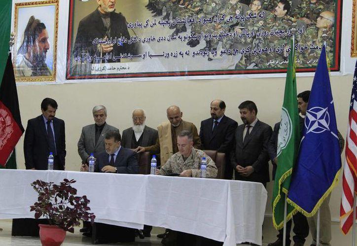 El máximo responsable de la misión de la OTAN y de las tropas estadounidenses en Afganistán, el general Joseph Dunford (cd), y el ministro afgano de Defensa, Bismilá Jan Mohamadi (ci), durante la ceremonia de entrega a las autoridades afganas del mando de la prisión de Bagram. (EFE)