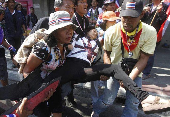 Opositores al Gobierno cargan a una de sus compañeras, herida por la explosión de una granada, durante las protestas contra el primera ministra, Yingluck Shinawatra. (Agencias)