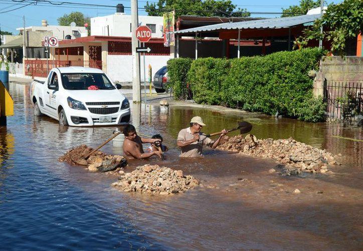 Personal de la Japay se tuvo que meter literalmente hasta el cuello para reparar la fuga de agua de la colonia Pensiones. (Cuauhtémoc Moreno/SIPSE)