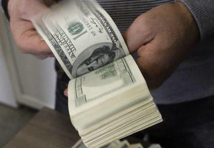 El dólar libre se cotizó en un máximo de 15.24 pesos, un incremento de 13 centavos respecto al pasado viernes. (Archivo/AP)