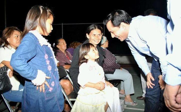 Mauricio Vila Dosal saluda a un par de niñas que asistieron con sus padres militantes panistas del II distrito. (Milenio Novedades)