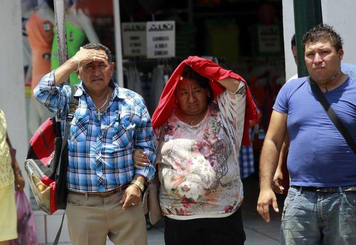 Yucatecos se protegieron como pudieron de los fuertes rayos del sol y de las agobiantes temperaturas. (Christian Ayala/SIPSE)