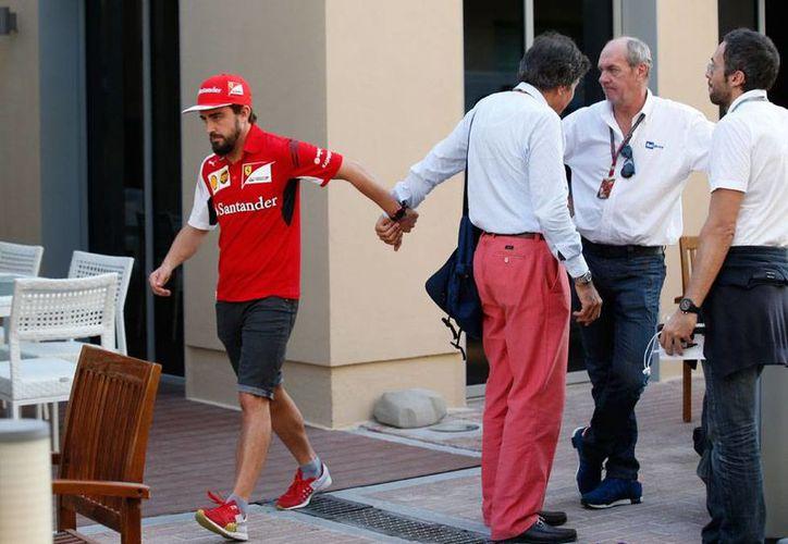 Fernando Alonzo se despide de los periodistas, tras conocerse la noticia de que se va definitivamente de la escudería Ferrari. La última carrera del español con el equipo italiano será la del Gran Premio de Abu Dabi. (AP)