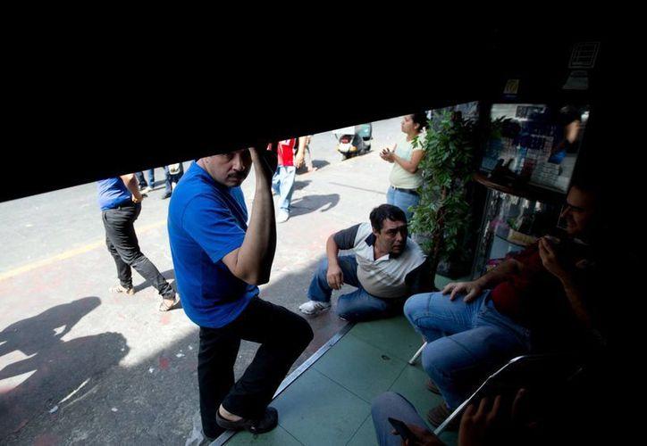 Empleados esperan fuera de su lugar de trabajo a que se restaure la energía en Caracas, Venezuela. (Agencias)