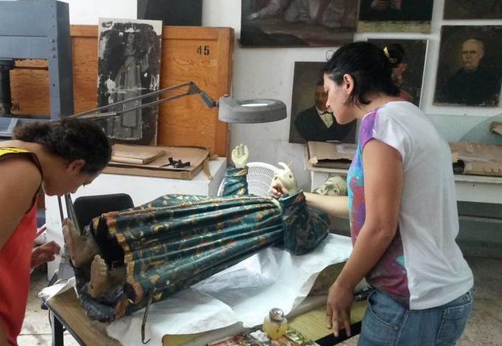 Expertas del INAH mientras restauran una imagen de San Francisco del municipio de Hocabá, patrono del lugar. (Ana Hernández/SIPSE)