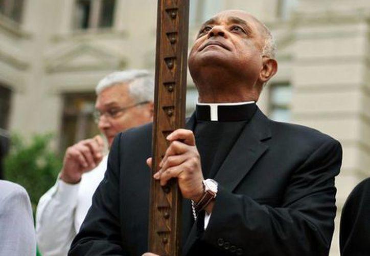 El arzobispo de Atlanta sostiene una cruz durante la 32 ª anual de peregrinación del Viernes Santo en el Parque Hurt en Atlanta. (Agencias)
