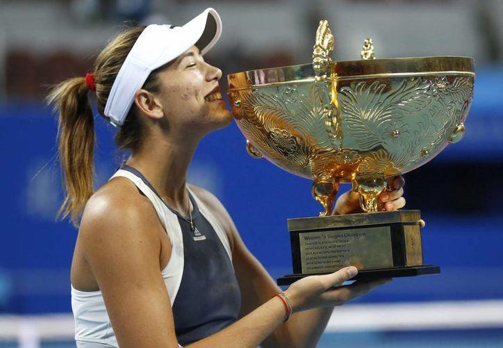 Garbiñe Muguruza, quien recién cumplió 22 años, besa el trofeo que la acredita como campeona del Abierto de China. (Fotos: EFE)