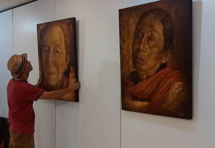 Imagen del pintor Juan Pablo Bavio al colocar sus pinturas en la galería del Aeropuerto Internacional de Mérida. (Foto tomada del Facebook Juan Pablo Bavio)