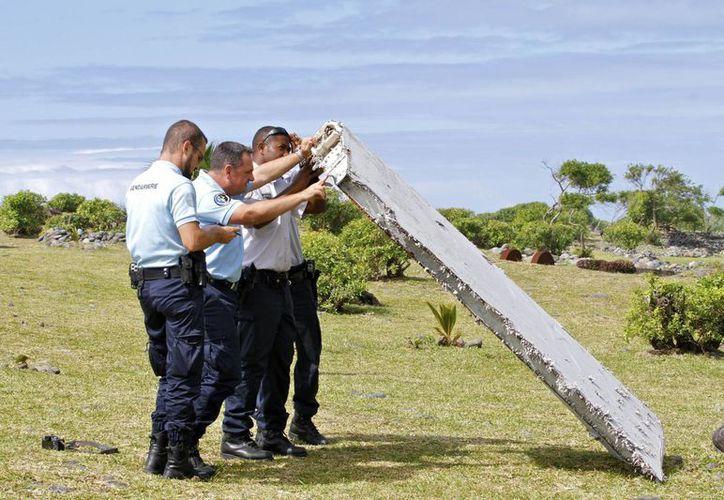 Varios miembros de la Gendarmería francesa inspeccionan el fragmento de un ala, la cual se confirmó que pertenece al avión desaparecido el 2014. (Agencias)