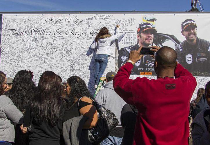 Miles de personas firmaron el muro dedicado a Paul Walker, en el sitio donde murió. (Agencias)