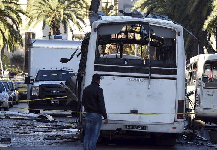 Un oficial camina al lado del autobús que explotó el martes en Túnez, ataque que se atribuyó el Estado Islámico. (Agencias)