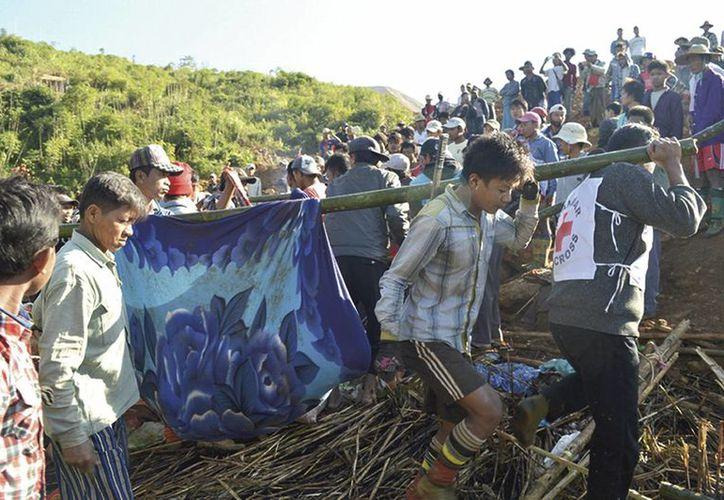 Trabajadores de la Cruz Roja de Mianmar y otras personas transportan a víctimas de un deslave en una zona afectada en la mina de jade de Phakant. (Agencias)
