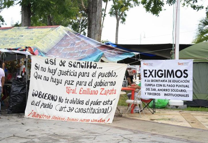 Permanecen frente al Palacio de Gobierno, a pesar de las condiciones climáticas. (Benjamín Pat/SIPSE)