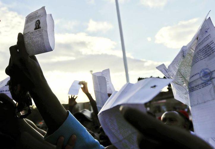 Inmigrantes haitianos sostienen sus documentos migratorios mexicanos mientras esperan obtener un lugar en la lista diaria para ingresar al lado estadounidense de la frontera desde Tijuana. (AP/Gregory Bull)