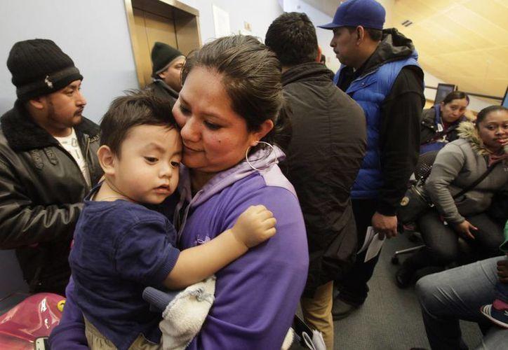 Verónica Ramírez, originaria de México, carga a su hijo de 15 meses, Lora, mientras espera formada para obtener la nueva cédula de identidad municipal que otorga la ciudad de Nueva York, en una biblioteca en el Bronx. (Agencias)