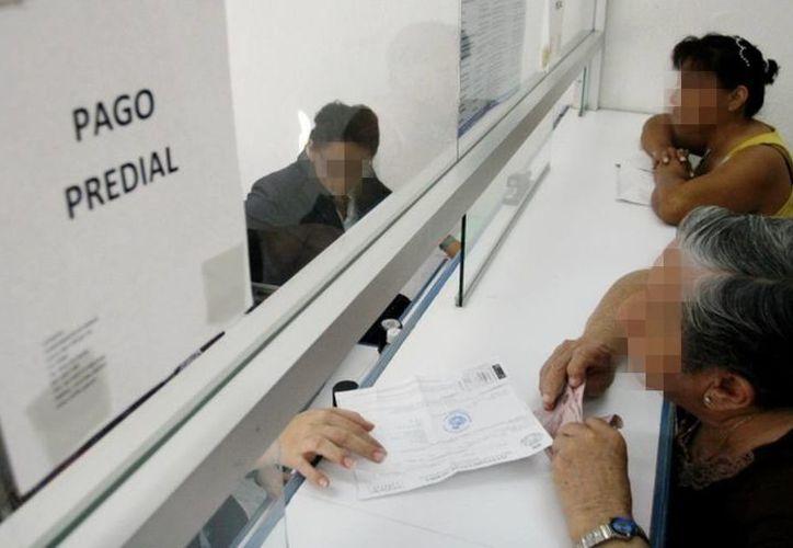 El Ayuntamiento meridano fijó topes para el cobro del impuesto predial. Imagen de dos mujeres al momento de pagar su pago catastral. (Archivo/SIPSE)