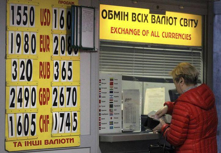 Una mujer cambia dinero en una oficina de cambio de divisa en Kiev, Ucrania. (EFE)