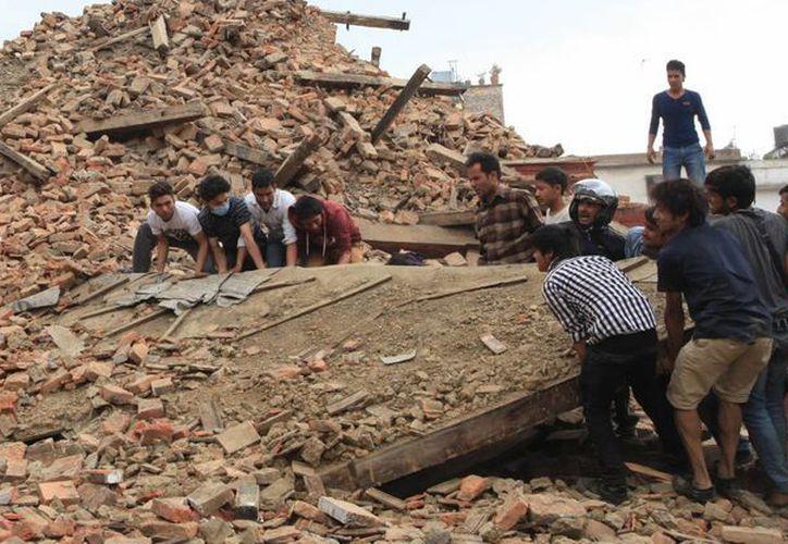 Un grupo de personas tratan de remover los escombros de un templo en Kathmandu, capital de Nepal, que sufrió el embate del sismo de 7.8 grados, este sábado. (Foto AP)