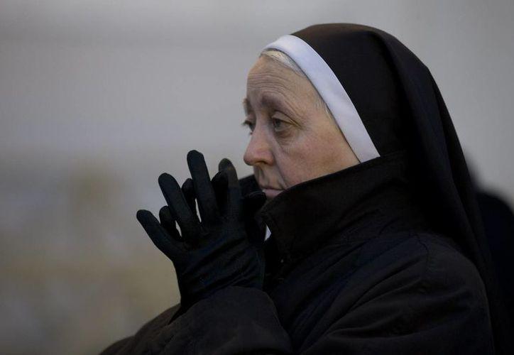 Una monja mira una pantalla gigante colocada bajo la estatua de St. Paul en la Plaza de San Pedro en el Vaticano, en la que se transmite la misa del Miércoles de Ceniza. (Agencias)