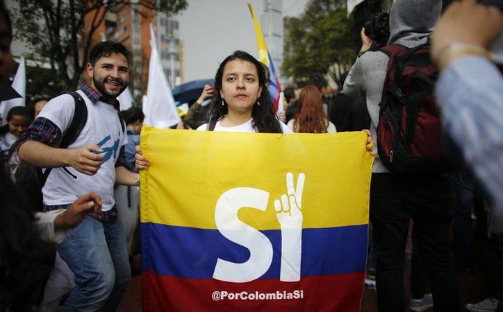 Una estudiante muestra una bandera de Colombia promoviendo el voto por el 'Sí'. (AP/Ariana Cubillos)