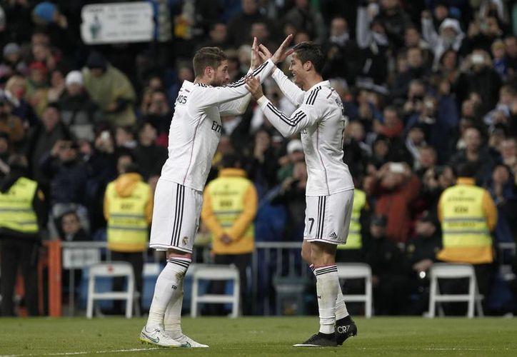 Cristiano Ronaldo (d), quien festeja un gol con Sergio Ramos, fue considerado por la Liga de España en el 11 ideal de diciembre. (Foto de archivo de Notimex)