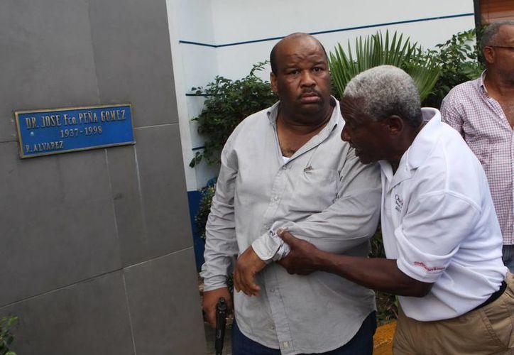 Un hombre intenta usar un arma en la sede del Partido Revolucionario Dominicano. (EFE)