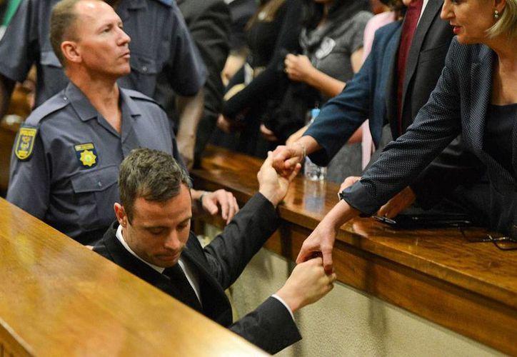 Oscar Pistorius, quien aparece en la imagen al salir de una audiencia, no podrá salir de la cárcel para pasar su condena en casa, debido a que el Departamento de Justicia ordenó analizar la resolución que le otorga la prisión domiciliaria. (AP)