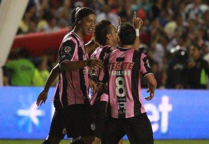 Camilo Sanvezzo (centro) y Ronaldinho festejan con el resto de los jugadores de Querétaro, que están muy cerca de clasificar a la liguilla. (mexsports.com)