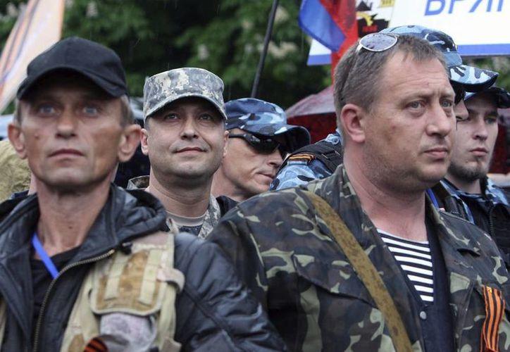 Un par de hombres prorrusos armados vigilan mientras el auto-declarado gobernador prorruso en la provincia de Lugansk, Valery Bolotov (c), comparece ante los residentes de este lugar. (EFE)